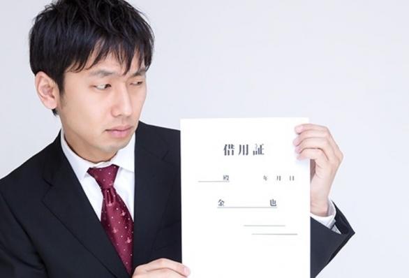 借用証を怪しむ男性(モデル:大川竜弥/Pakutaso)